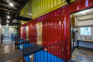 Các phòng ngủ được đặt trong 3 container cũ sơn vàng, xanh, đỏ tượng trưng cho 3 loại phòng