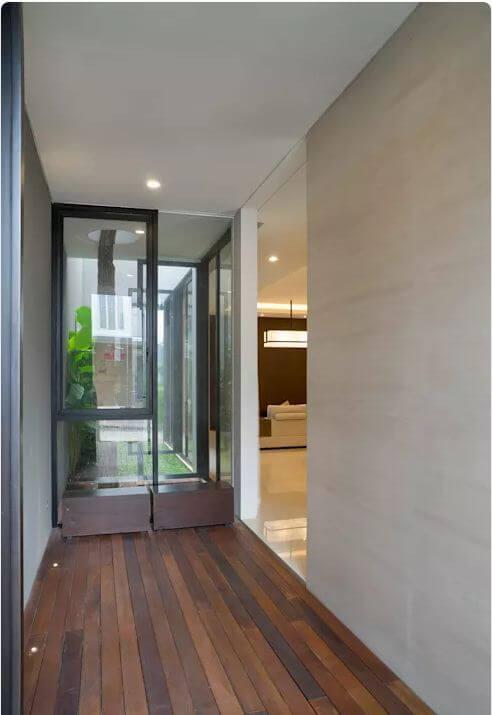 Hành lang lát gỗ mộc mạc - Ngôi nhà phố 2 tầng hiện đại đẹp