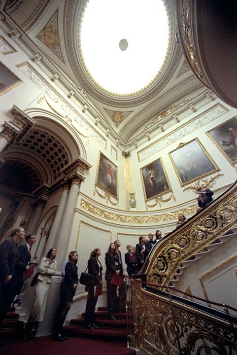 Bước chân vào cung điện này, bạn sẽ bắt gặp cầu thang lớn được trải thảm đỏ dẫn lối tới phòng khánh tiết (State Rooms). Những bức ảnh chân dung thành viên hoàng gia được treo dọc theo tường cầu thang. (Ảnh: Hellomagazine)