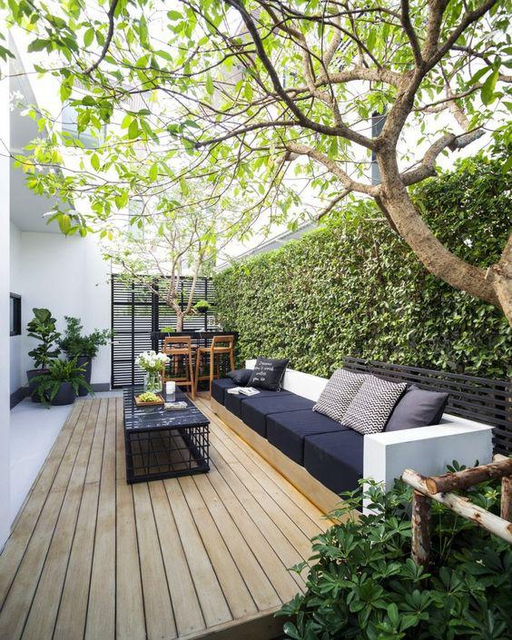 Mẫu thiết kế góc thư giãn lý tưởng nơi sân vườn với sàn ốp gỗ, tường cây xanh mát mắt.